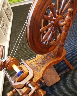 Spinning wheel made by Tom Jones with decorative carving of oak leaves